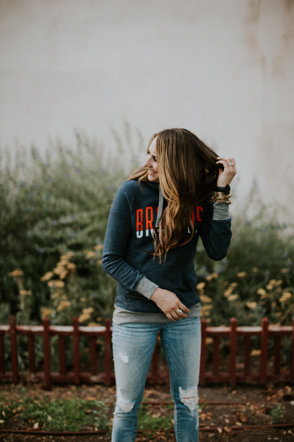 Womens NFL Broncos Hoodie girl wearing navy Denver Broncos Hoodie with brown curled hair and skinny distressed denim