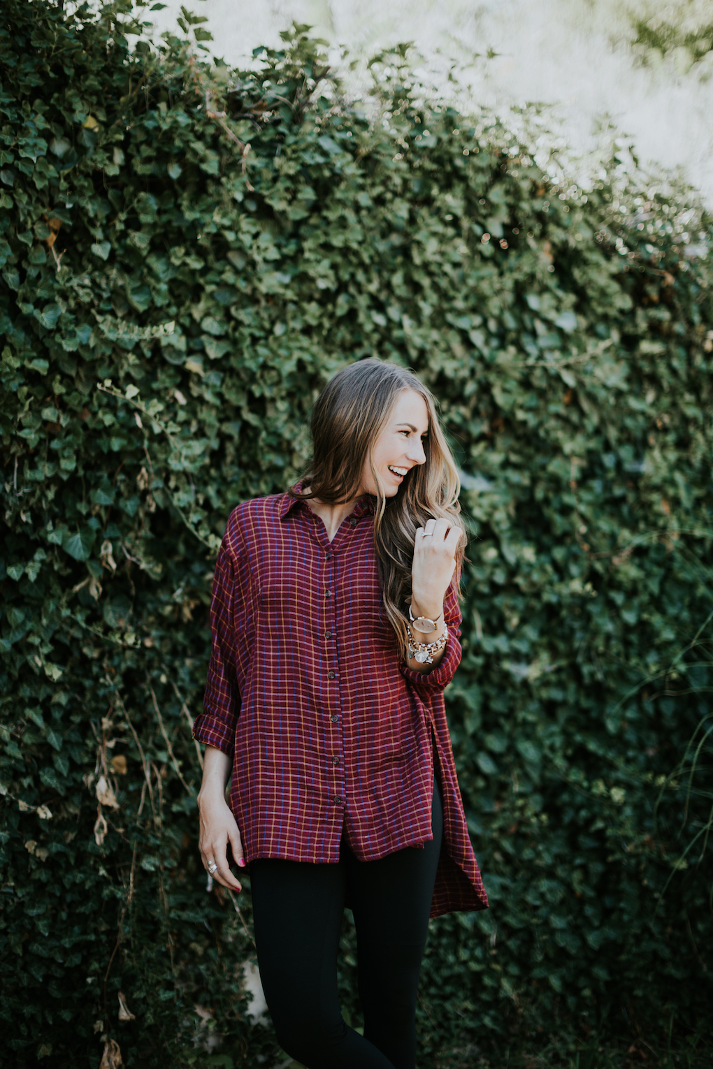 Girl laughing wearing red oversized flannel with leggings.