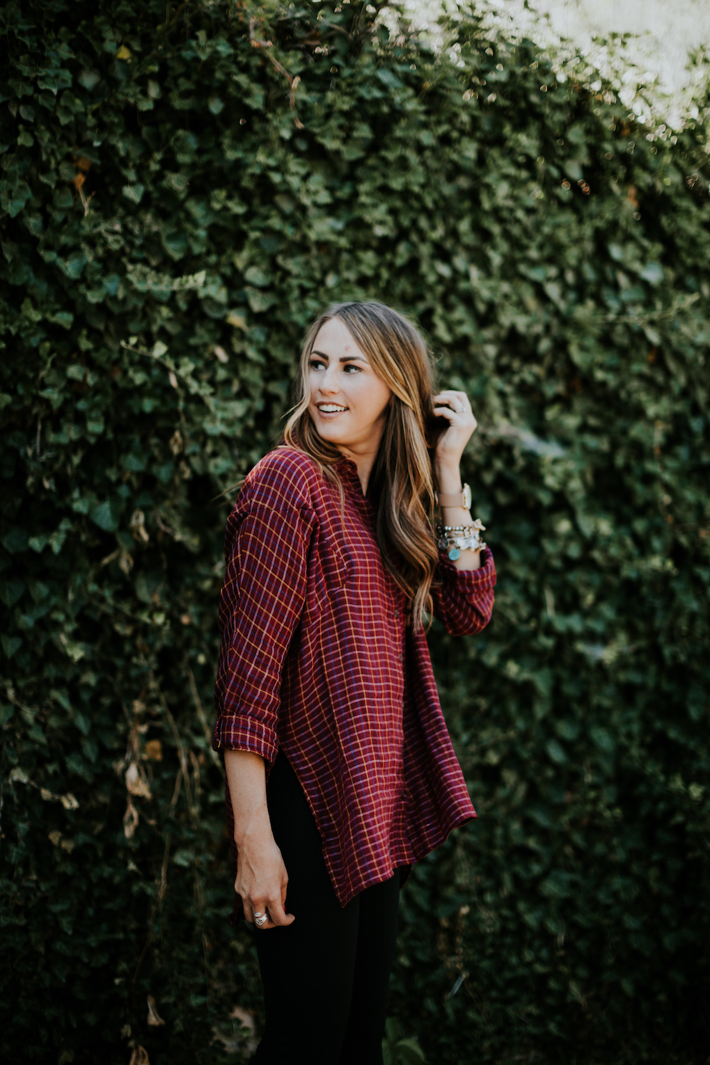 girl turned side ways laughing in red oversized flannel