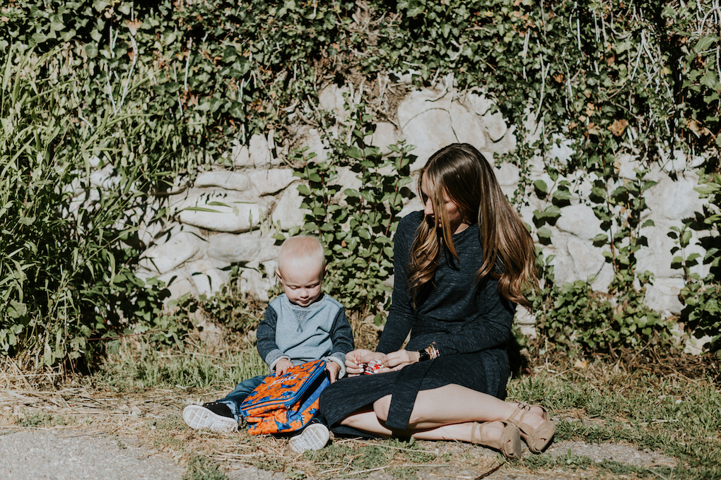 mom in navy tie dress little boy in crew neck sweatshirt with denim joggers on sitting on the cement with vines behind them and a dinosaur lunch box