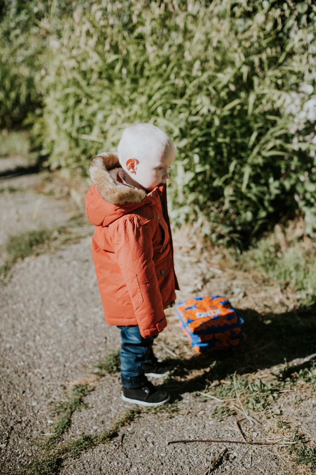little boy running in orange coat with fur on the hood and denim joggers with black toms