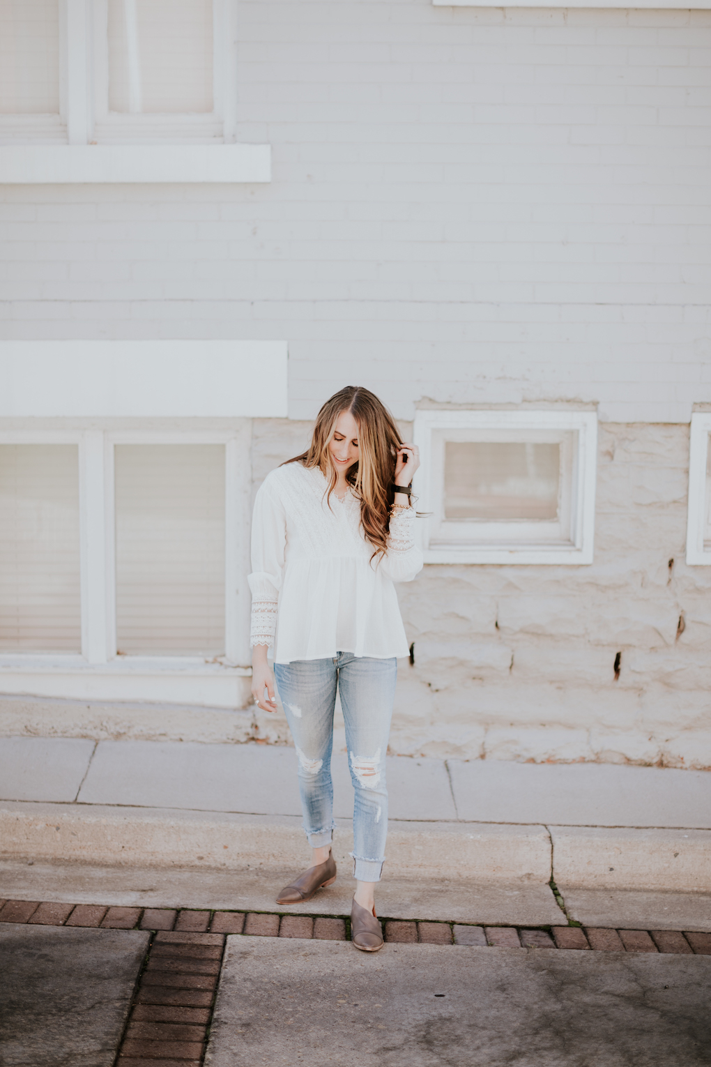 Girl wearing white textured top with distressed light denim skinny jeans and free people booties