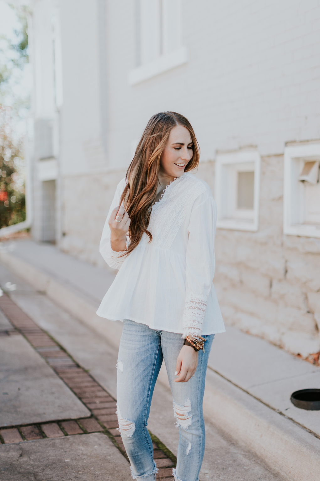 girl with brown hair and caramel highlights wearing white long sleeve lace detail top