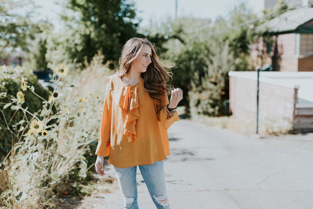 girl with brown caramel hair wearing mustard orange sheer ruffle top with distressed jeans