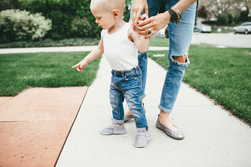 mom and toddler boy walking down sidewalk little boy in white wife beater tank top and distressed jeans with freshly picked moccs