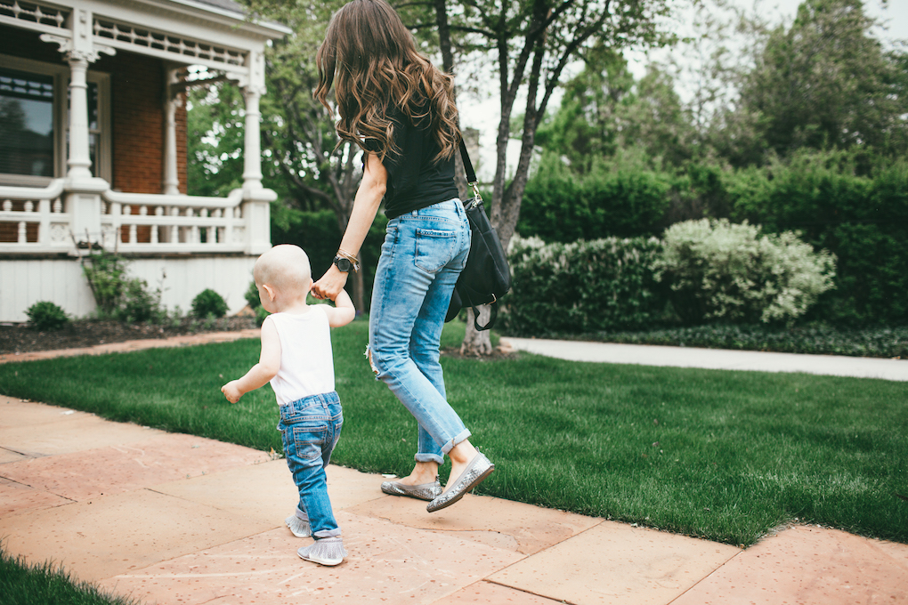 mom and toddler boy walking down sidewalk little boy in white wife beater tank top and distressed jeans with freshly picked moccs mom in distressed denim with black free people top yosi samra flats and black fawn design bag