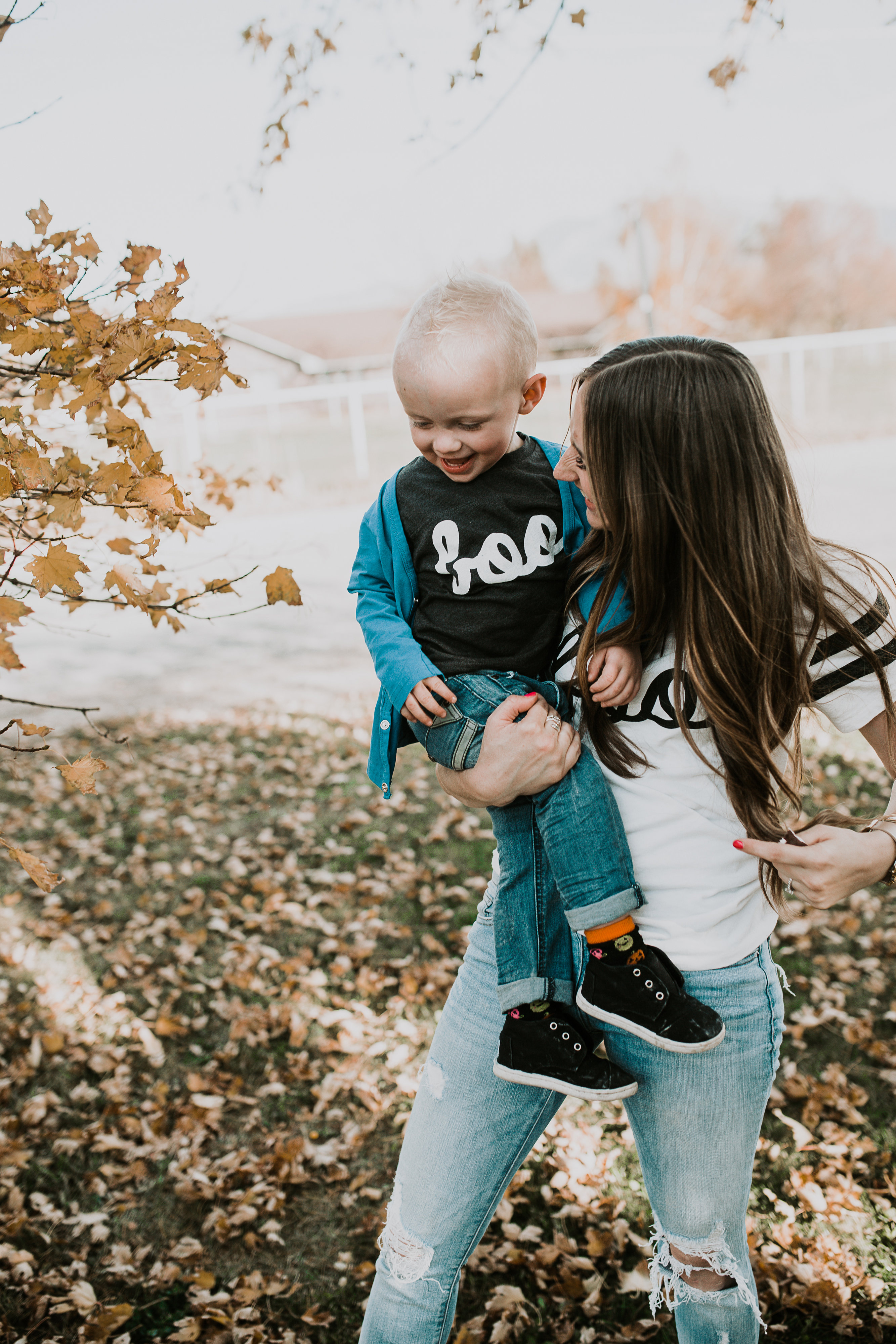 mom and little boy in BOO halloween tees playing in the leaves mom has light brown loosely curled hair and wearing distressed denim little boy in june and january cardigan
