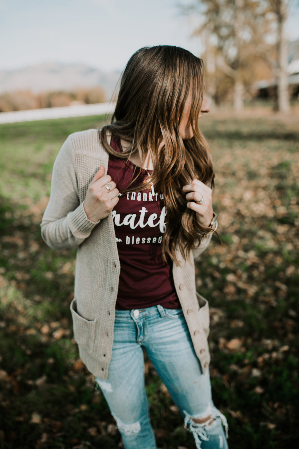 girl standing in field in wine colored grateful tee a long cream cardigan and distressed denim jeans with loosely curled brown hair