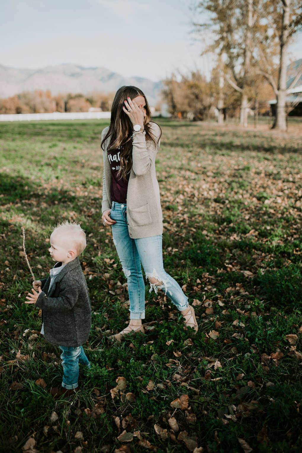 mom and little boy playing in field little boy in tweed jacket and plaid button up shirt with skinny jeans and brown boots mom in long cream cardigan a wine colored grateful tee and distressed denim