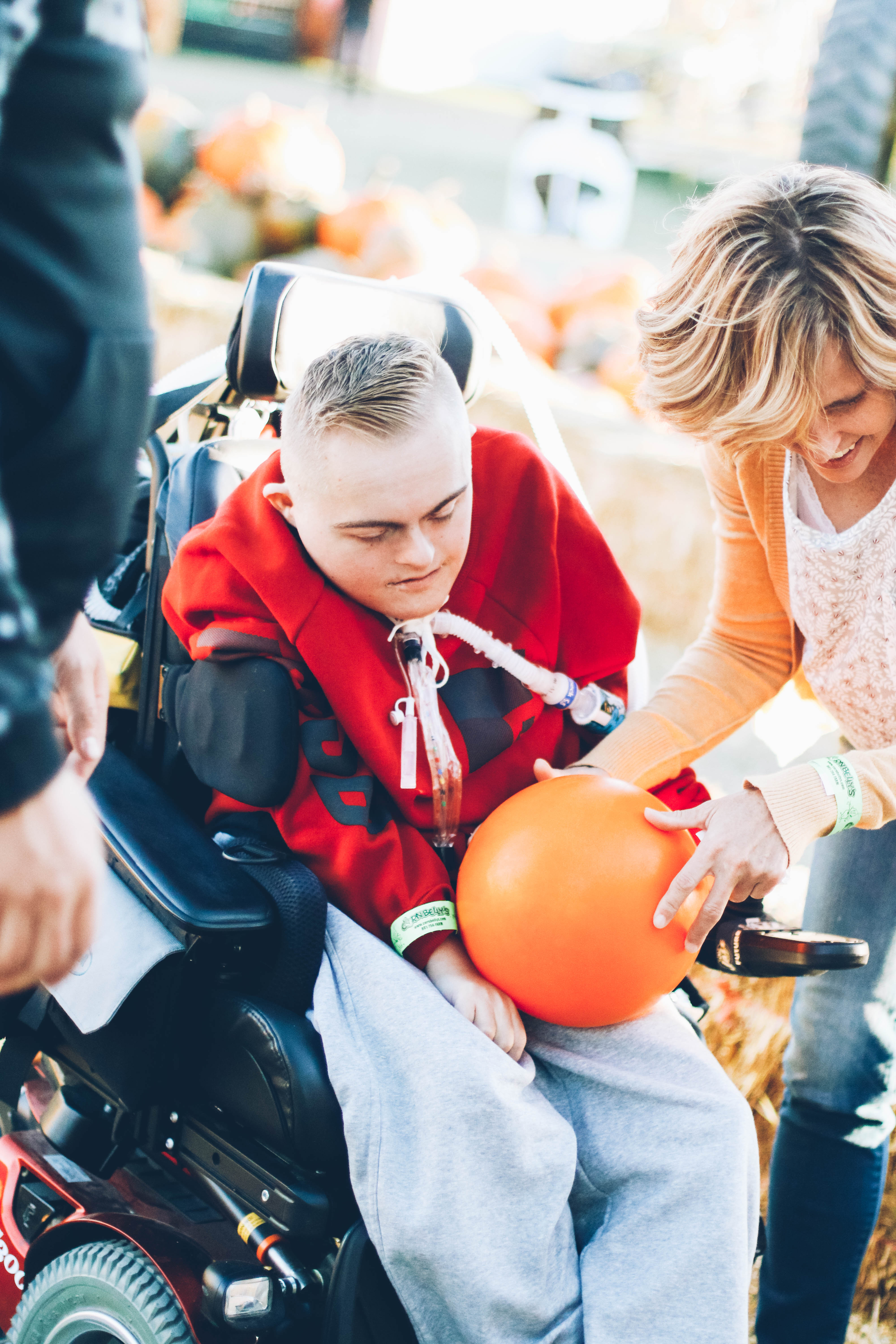 mom and special needs boy playing pumpkin bowling at corn maze