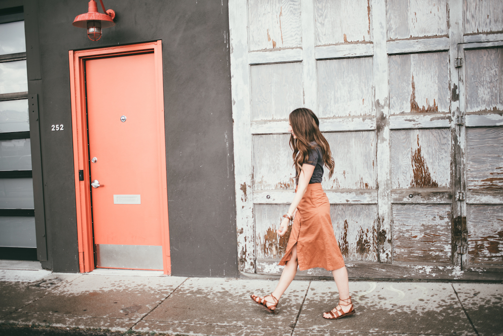 orange button up midi skirt with grey tee shirt girl standing in front of old distressed white garage door