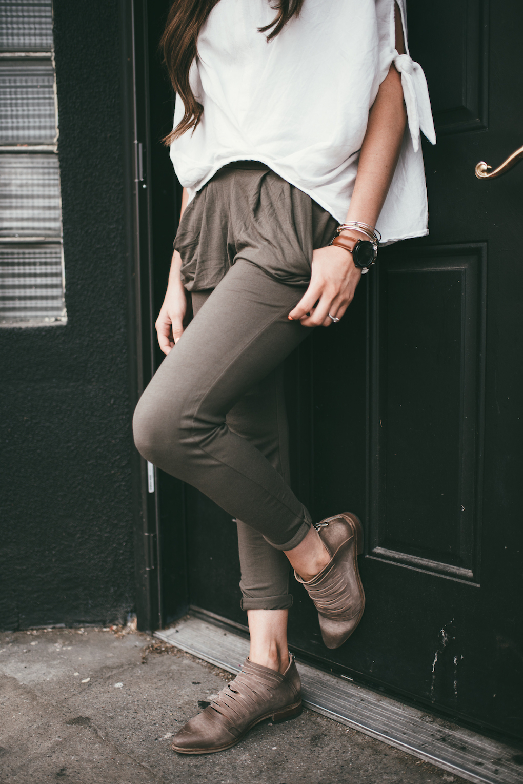 olive green knit green pants with oversized white top on girl standing in front of all black doorway with long brown curled hair
