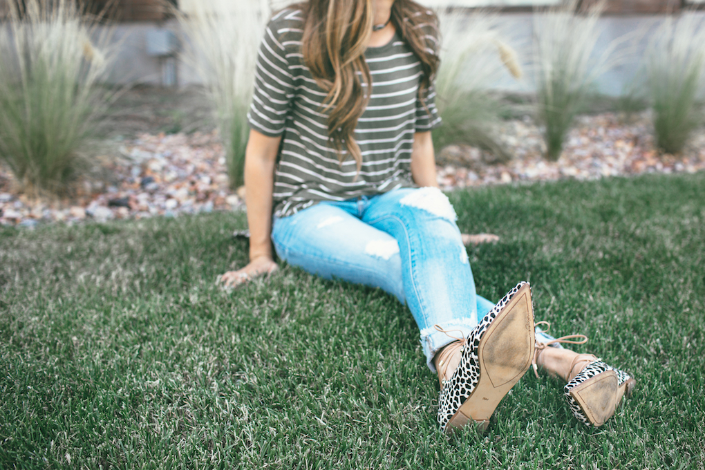 girl sitting on the grass wearing a stripe green shirt distressed denim and leopard tie flats