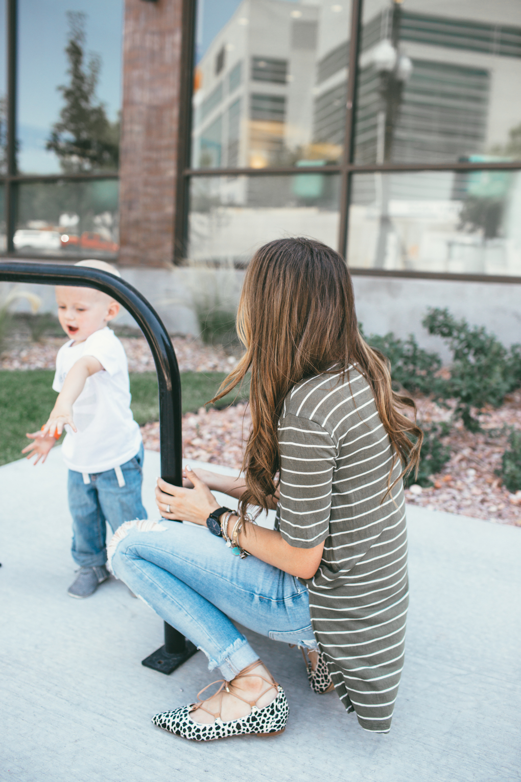 mom and little boy playing on the grass mom in distressed denim green stripe shirt and leopard flats looking at little boy playing in the distance little boy in skinny jeans moccasins and a graphic tee