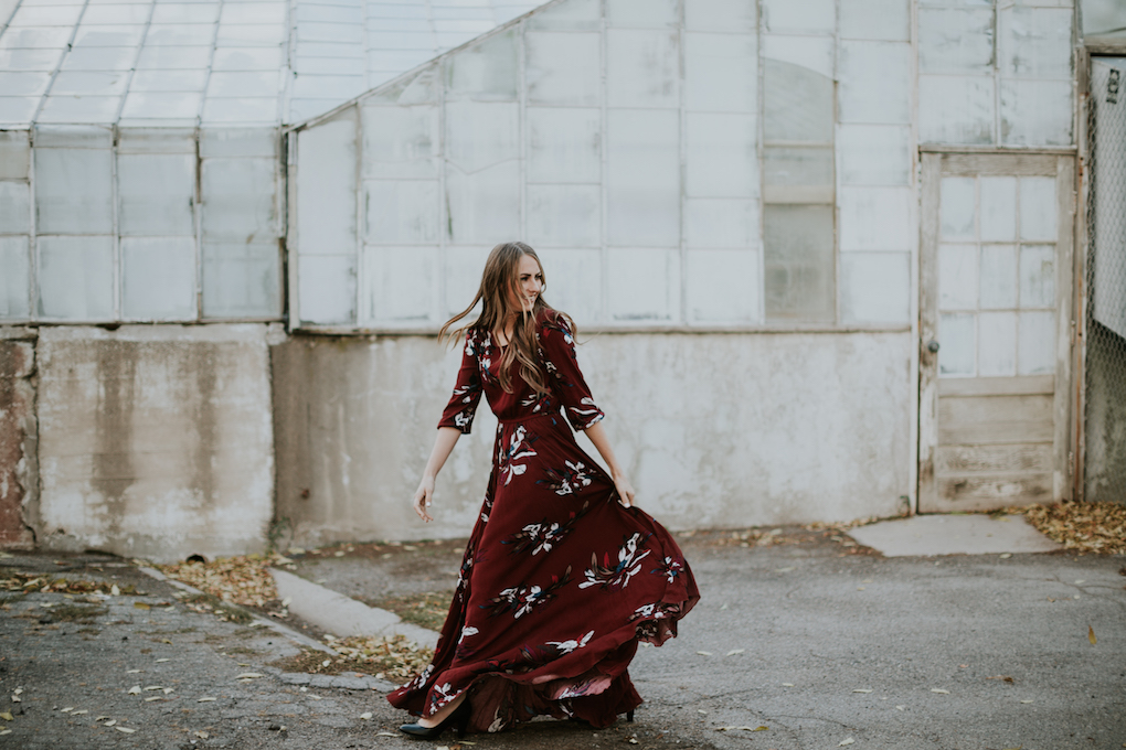 floral maroon maxi dress with girl standing in front of a green house with long brown loosely curled hair with caramel highlights