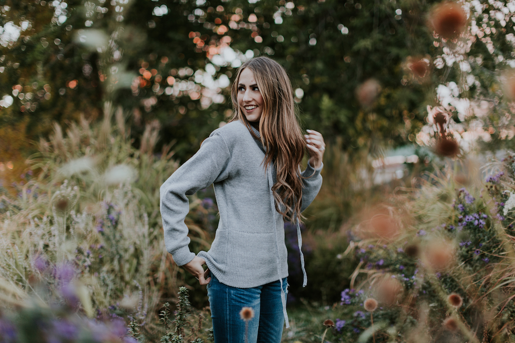 girl in grey lace sweater and distressed jeans standing in greenery with long caramel brown hair loosely curled