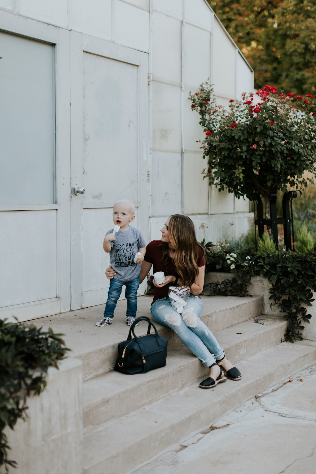 mom and little boy sitting on the stairs with baby pibu products little boy in graphic tee and jeans mom in distressed denim a maroon top and a navy handbag