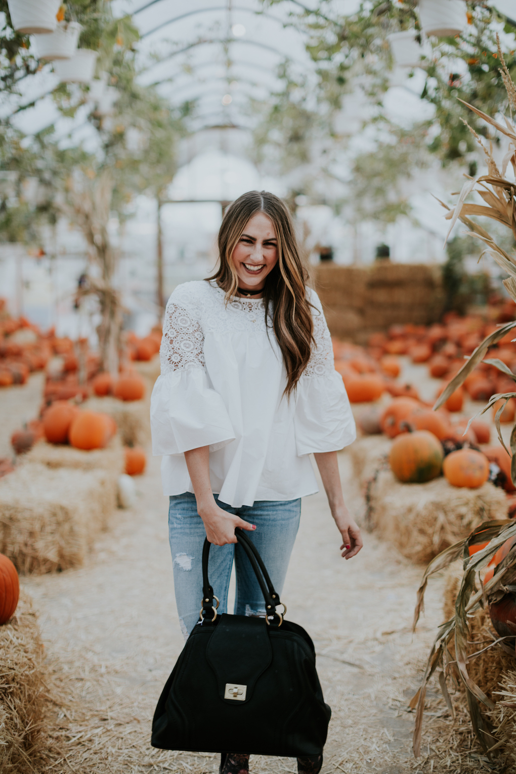 girl wearing white lace top with distressed denim and brown booties standing in a pumpkin patch with black diaper bag