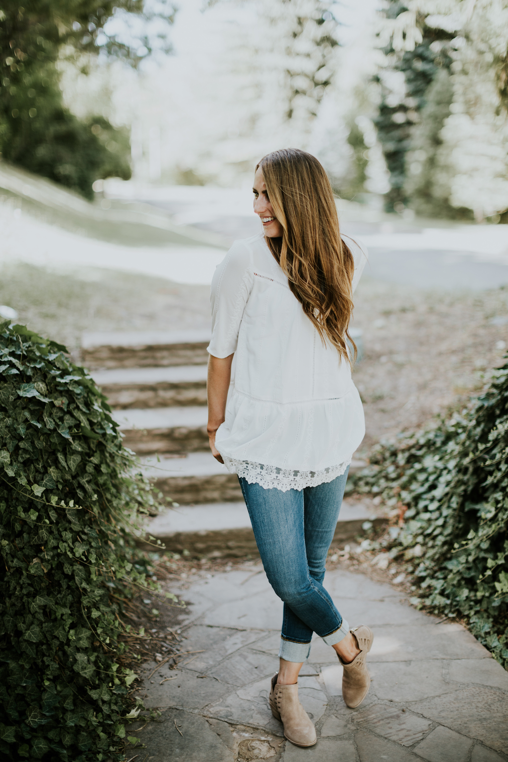 girl standing in white lace top with jeans and brown booties on long brown loosely curled hair with caramel highlights