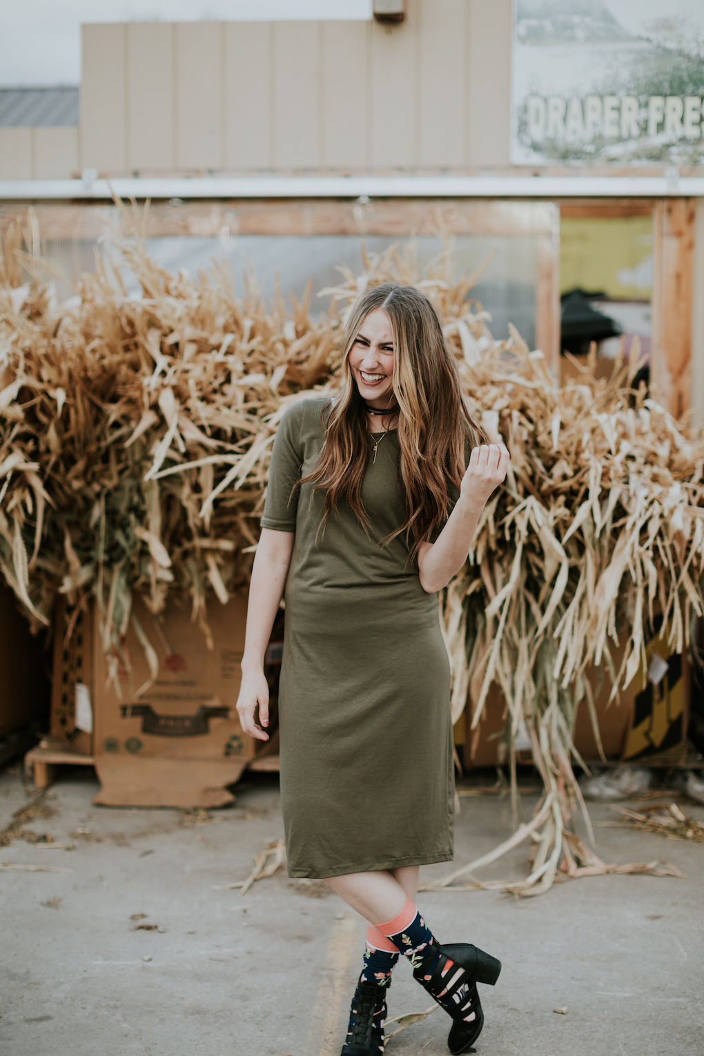 girl standing in front of cornstalks wearing a green midi dress, tall floral socks, strap black booties, and a choker with long brown caramel hair loosely curled