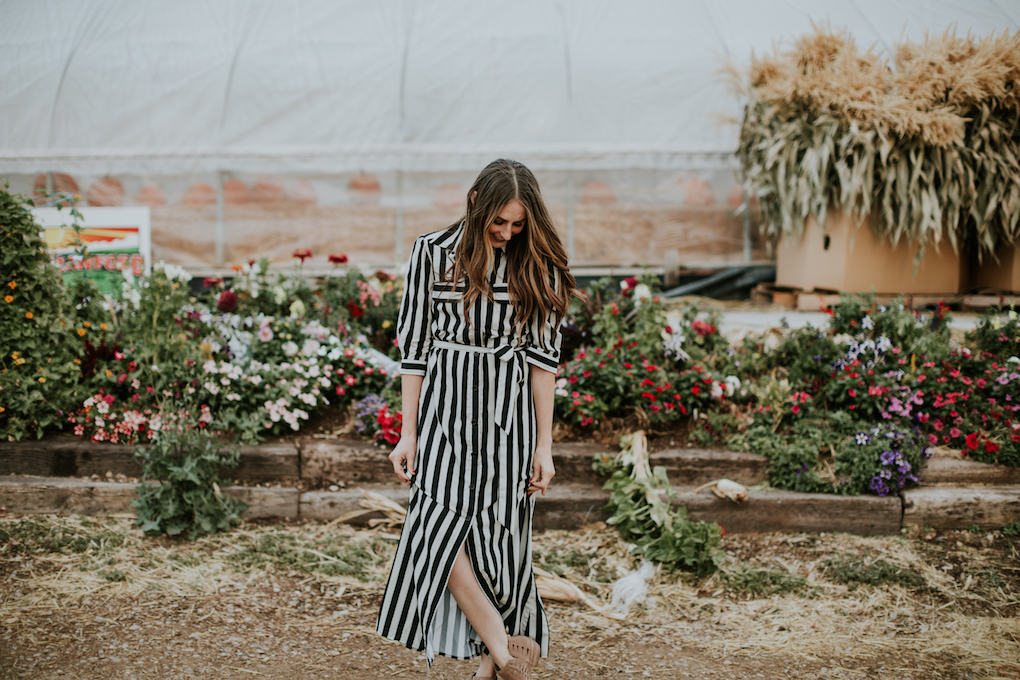girl standing in front of green house pumpkin patch wearing a black and white stripe long maxi dress with loosely curled brown hair with caramel highlights