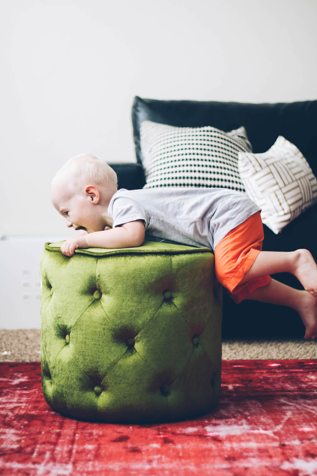 little boy climbing on green ottoman in living room with pink rug
