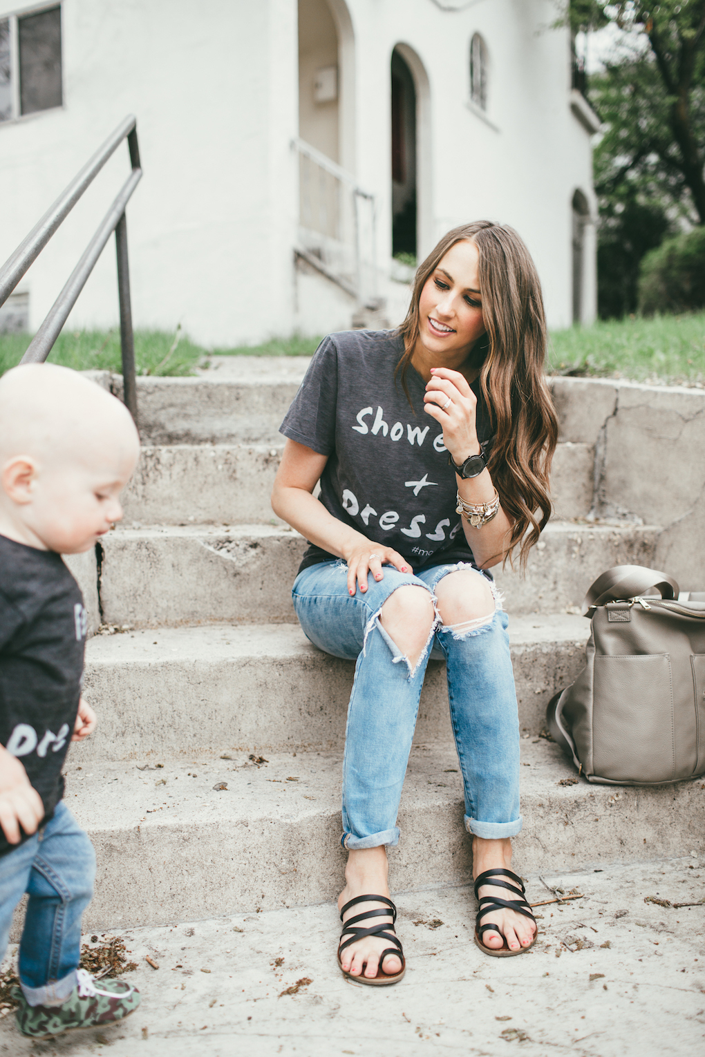 Mom and little boy in matching graphic tees, distressed denim sitting on cement stairs with a Fawn Design bag in Grey