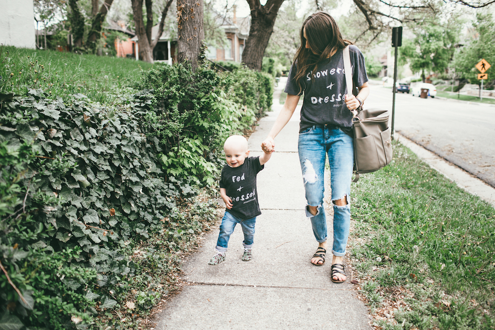 Mom and little boy in matching graphic tees, distressed denim walking down sidewalk with a Fawn Design bag in Grey