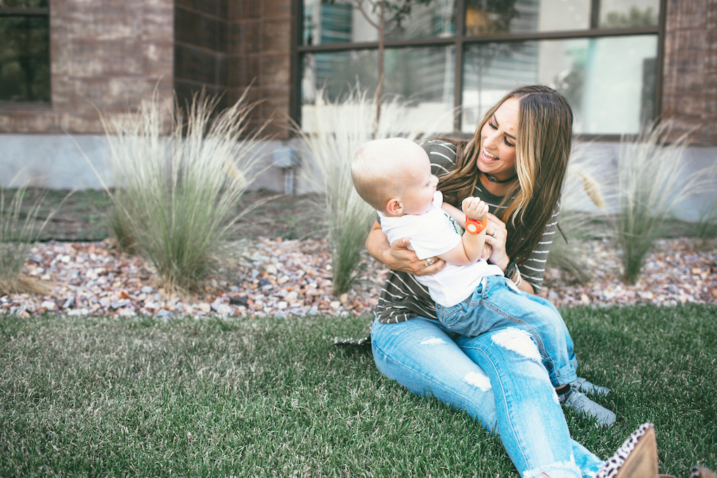 mom and little boy playing on the grass mom in distressed denim green stripe shirt and leopard flats looking at little boy laughing little boy in skinny jeans moccasins and a graphic tee