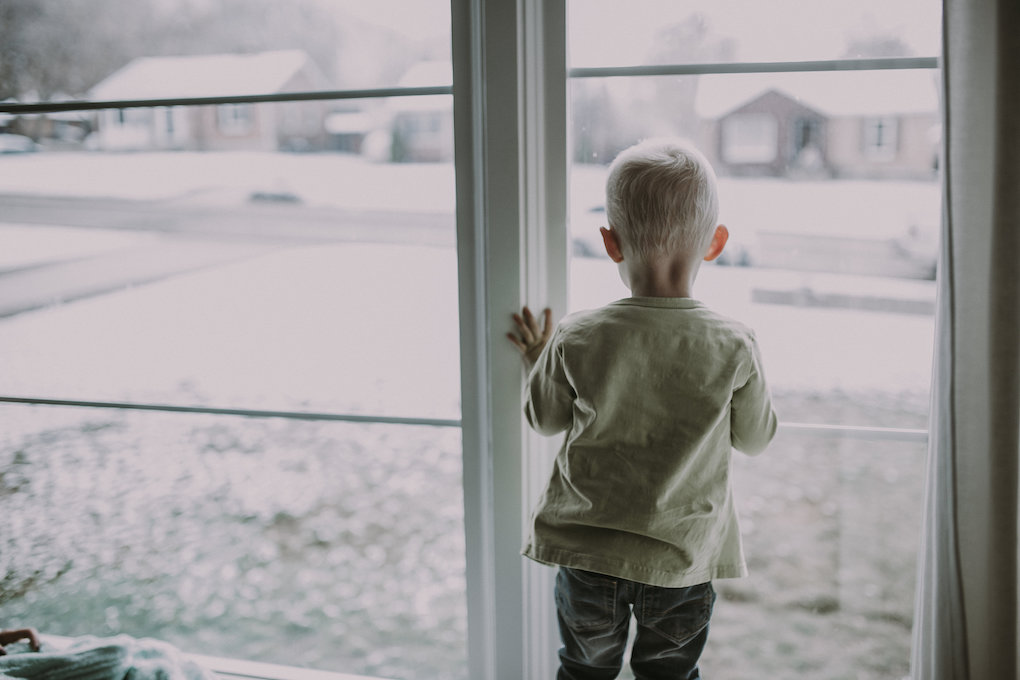 little boy sitting in window wearing june and january