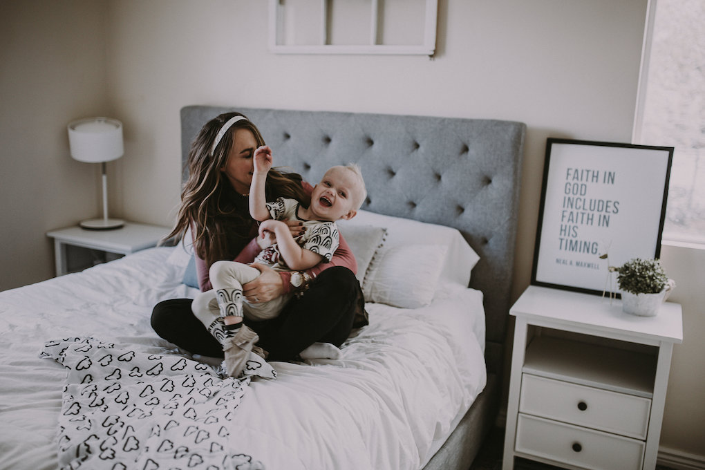 girl sitting on bed giggling in pink top with latterday home print and owl be sweatin headband lisa leonard ring and arvo watch with little boy in rags to raches and freshly picked moccasins