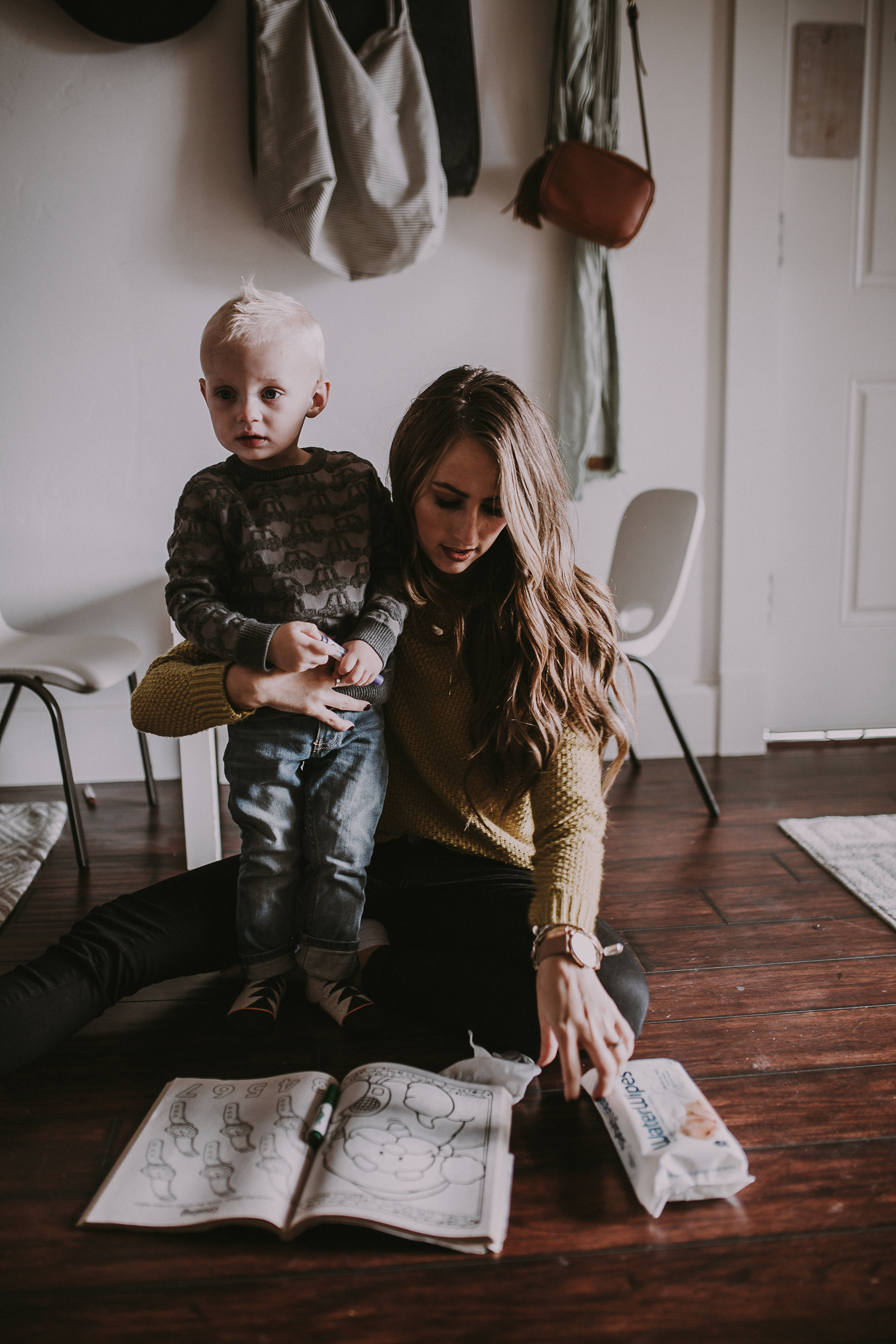 mom and little boy coloring at kids table christmas picturew mom in a mustard sweater little boy in a grey cars sweater with waterwipes