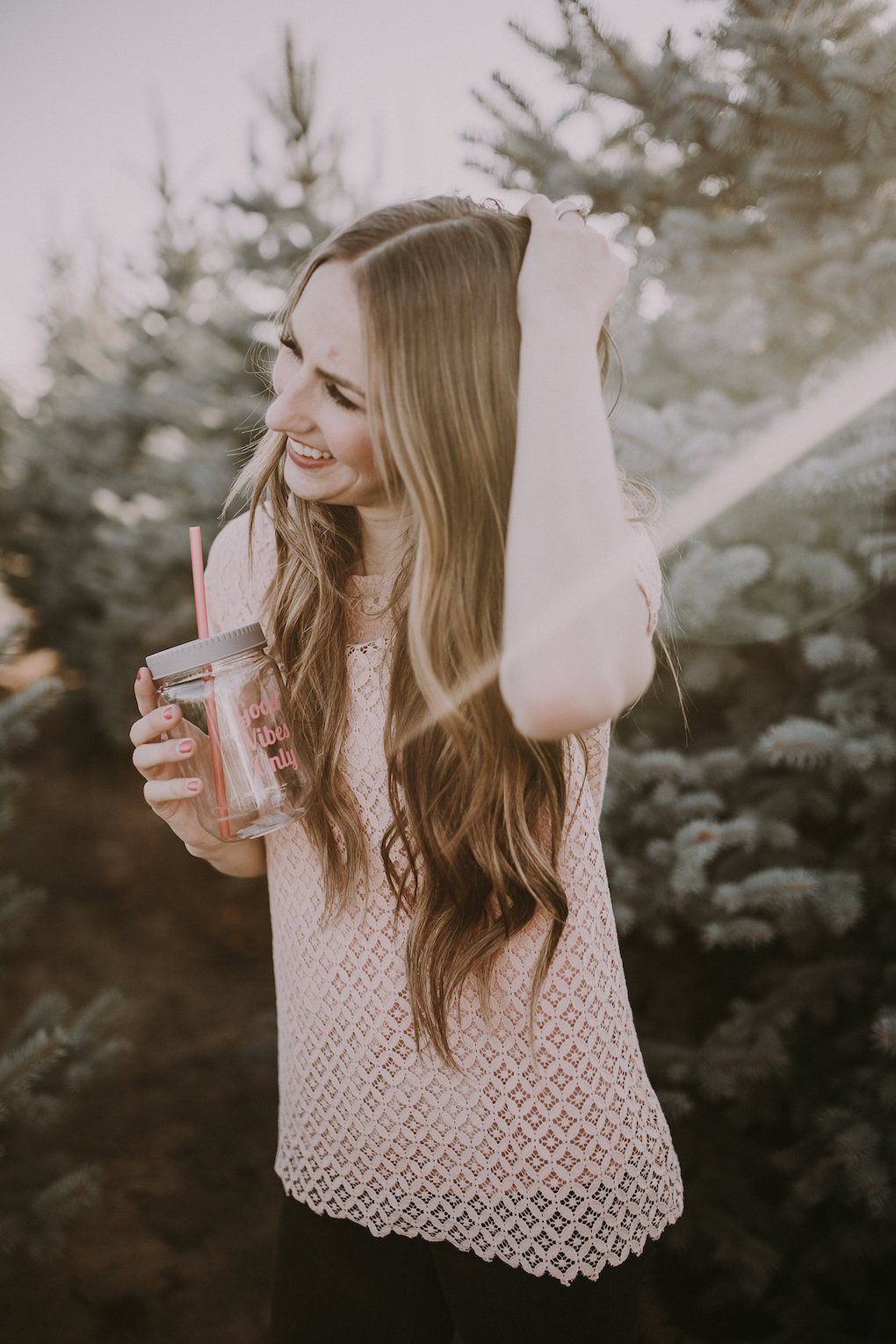 girl standing in Christmas Tree farm with long loosely curled brown hair with caramel highlights wearing downeast lace pink top with knitted thick cream cardigan and black jeggings