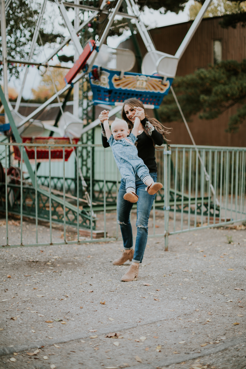 mom and little boy playing at amusement park little boy in rags to raches romper and freshly picked moccasins mom in free people thermal top skinny jeans and brown booties