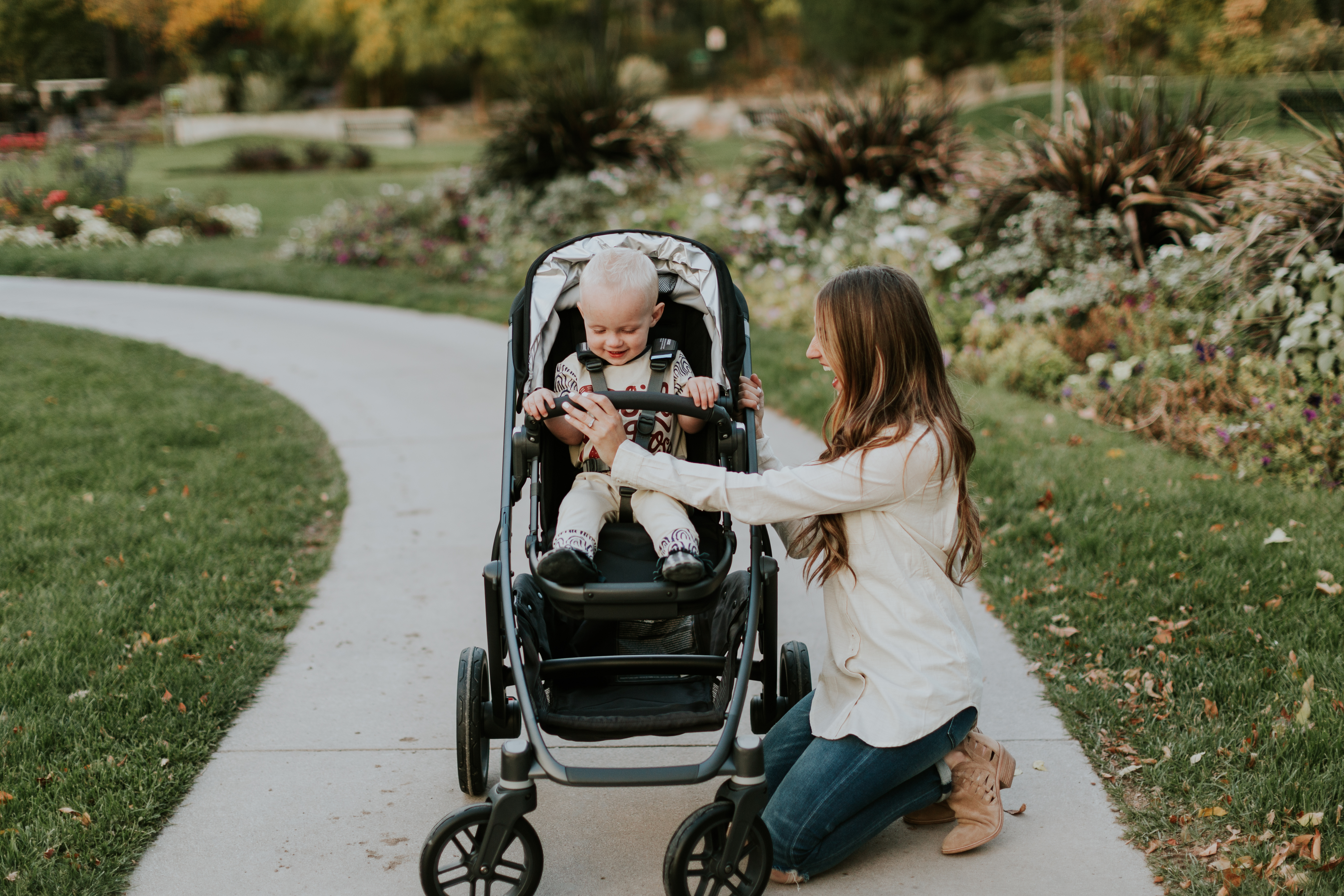 mom and little boy on sidewalk with little boy in rags to raches romper and mom in lila p cream top pushing uppa baby stroller