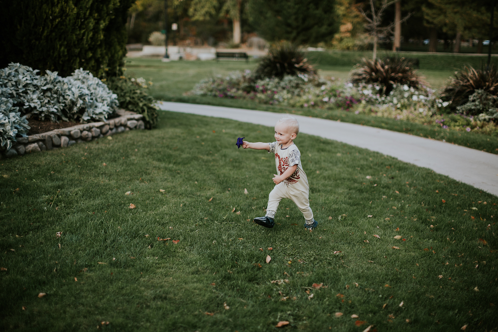 little boy standing in the grass in rags to raches romper playing