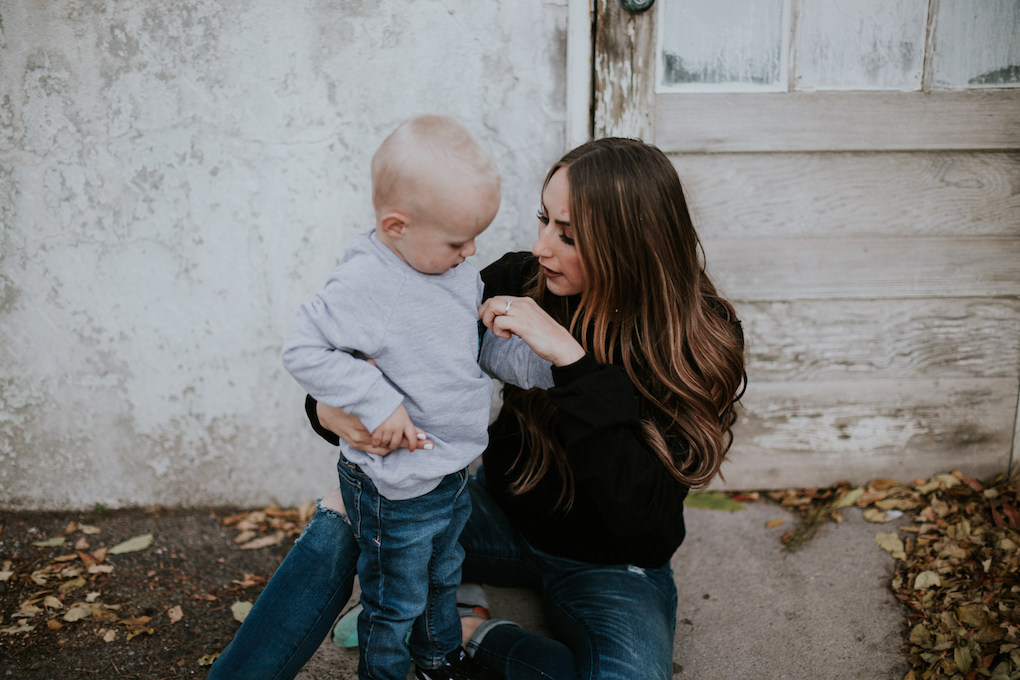 mom and little boy sitting in front of green house in senerge tee sweatshirts with patterned fabric pockets