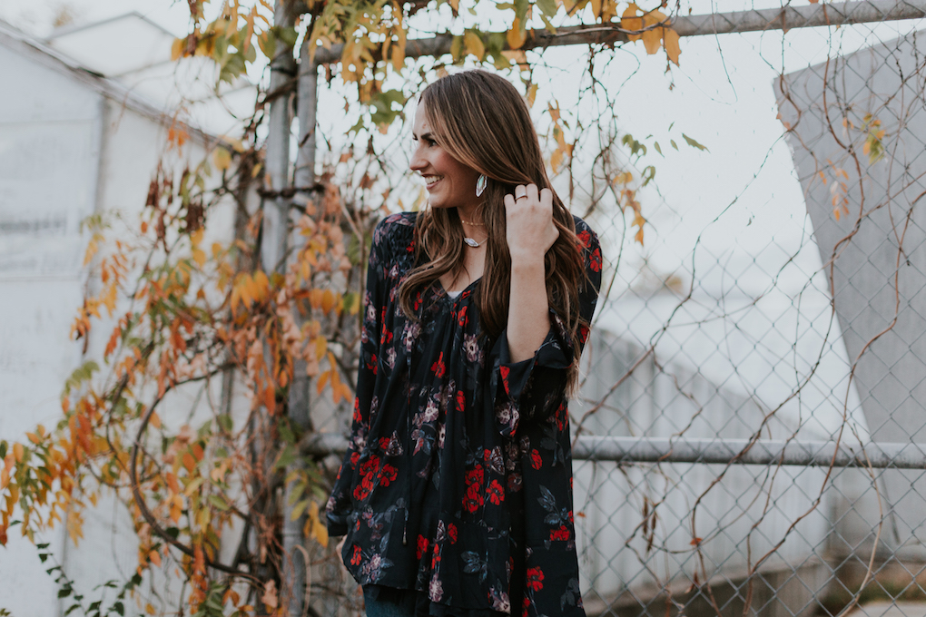 free people long floral navy top with dainty layered necklaces distressed jeans booties long loose curled brown hair with caramel highlights