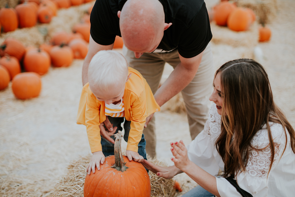 family playing at pumpkin patch mom in white lace top with skinny jeans dad in khaki pants and black tee little boy in june and january newlie diaper bag