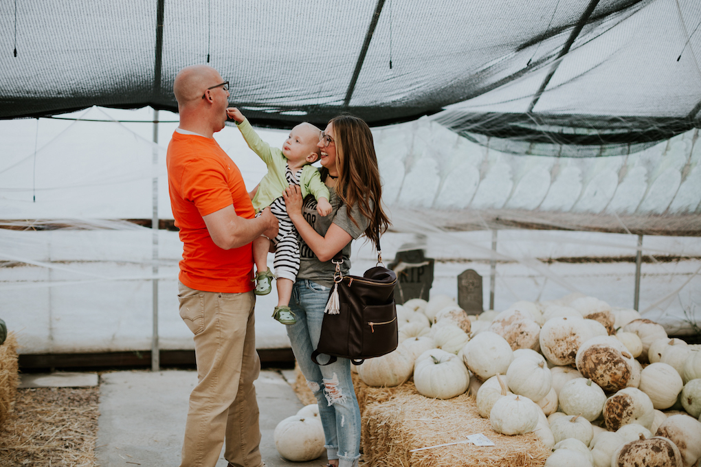 family sitting and laughing at the pumpkin patch mom in grey tee and glasses with distressed jeans dad in orange tee and khaki pants little boy in black and white romper and green cardigan