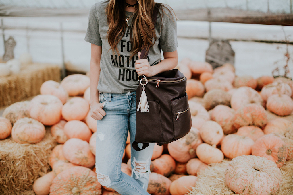 girl standing in pumpkin patch with grey graphic tee distressed jeans and plum fawn design bag