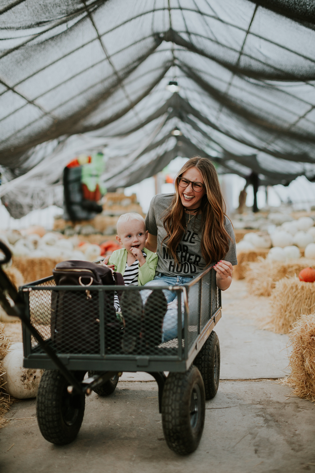 mom and little boy sitting in wagon at the pumpkin patch
