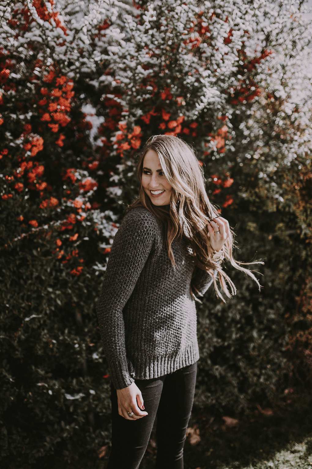 girl standing in front of berry bush wearing a thick oversized grey knit turtleneck with black jeans and black booties with brown loosely curled hair