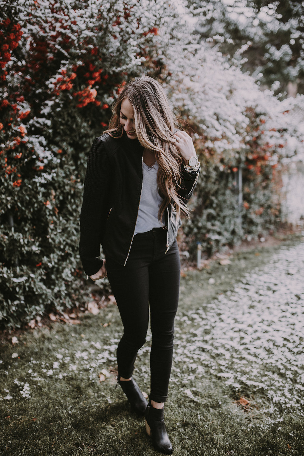 girl standing in front of berry bush wearing a black leather jacket and basic white tee paired with black jeans with holes in the knees and blcak booties with brown loosely curled hair