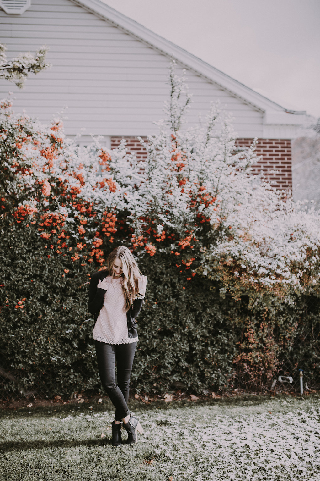 girl standing in front of berry bush wearing a light pink lace top with a black cardigan and black distressed jeans and blck booties with brown loosely curled hair