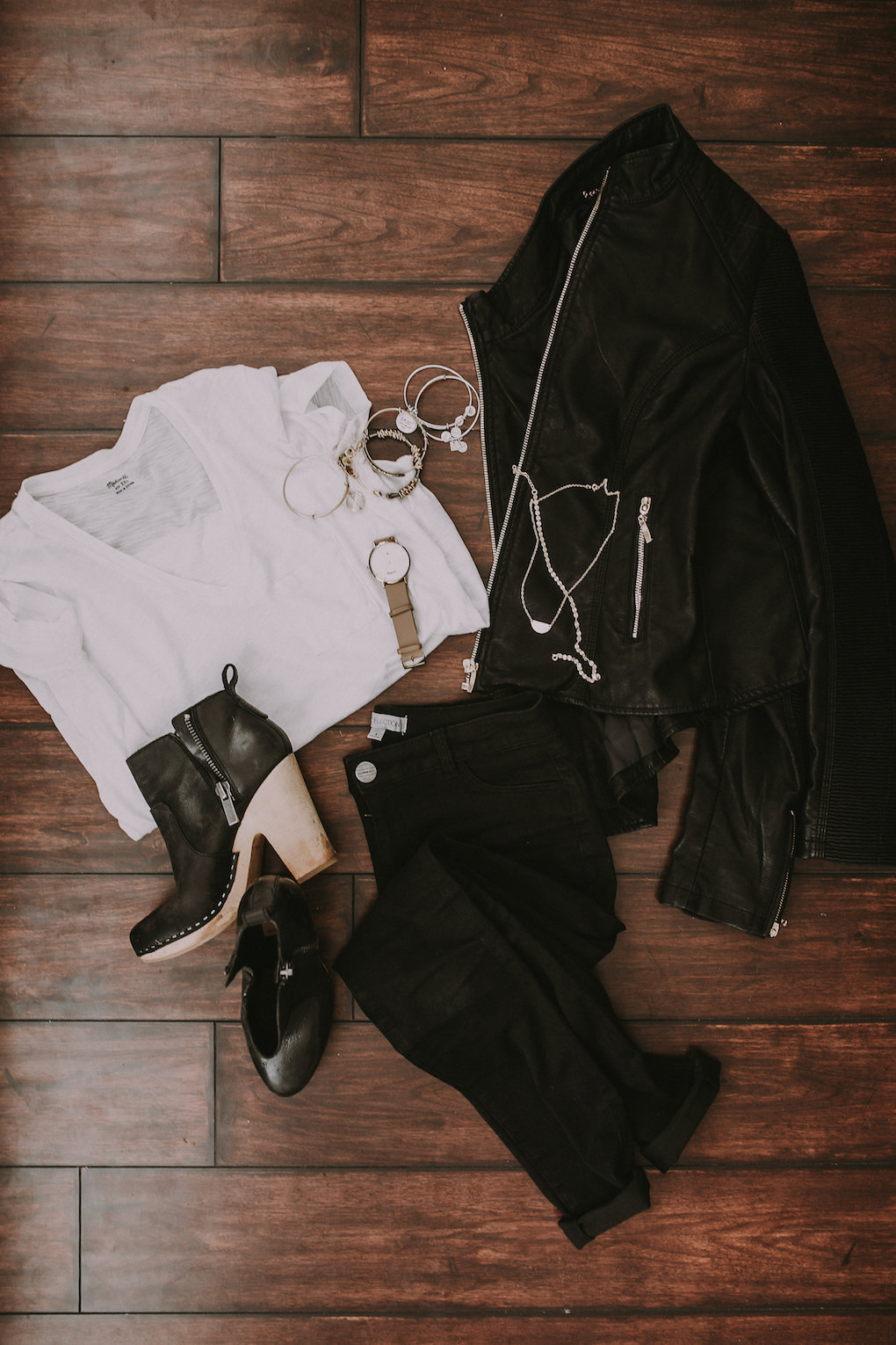 black leather jacket and basic white tee paired with black jeans with holes in the knees and blcak booties