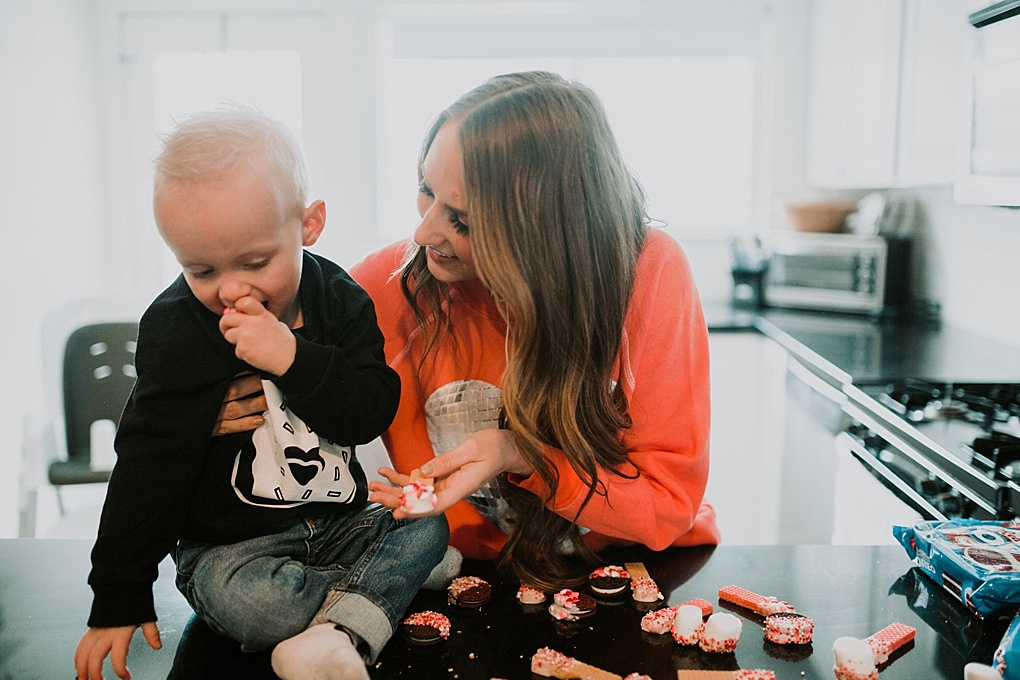 mom and little boy sitting in kitchen wearing valentines sweatshirts making 3 5 minute valentine treat recipes to make with your toddler chocolate dipped wafer cookies oreos and marshmallows
