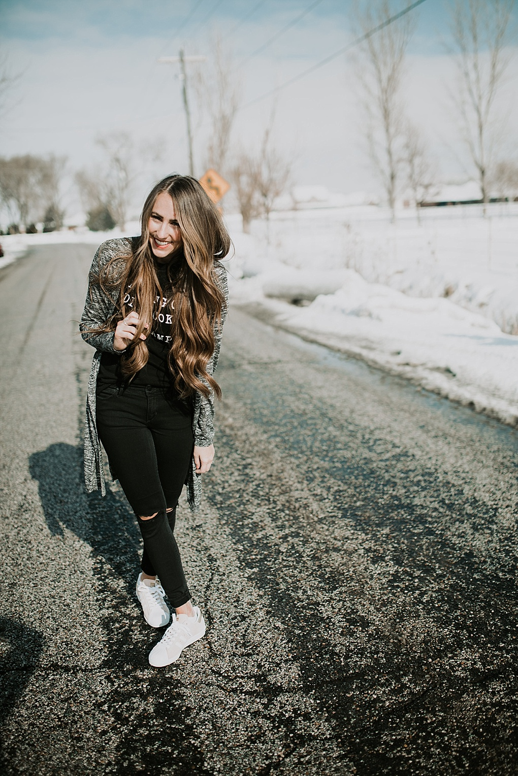 girl standing in road in black jeans with black tee shirt and long heathered grey black duster cardigan and blush pink adidas sneakers