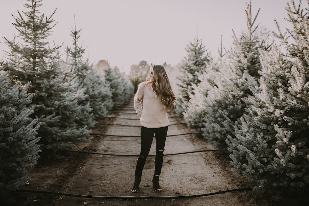 girl standing in tree farm in tan sweater with black jeans and peep toe toms booties