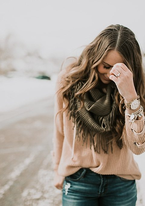 girl wearing infinity scarf with tan knit sweater and olive green fringe scarf nike boots and distressed jeans long loose brown curled hair with caramel highlights